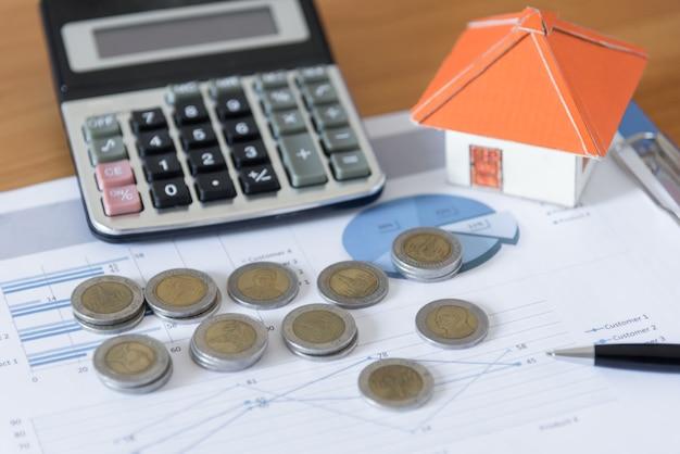 ペーパーハウス、ビジネス文書チャートのオフィスデスクの背景に電卓とコインスタック