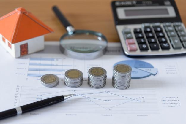 ビジネス文書のチャートのオフィスデスクの背景に電卓とペーパーハウス