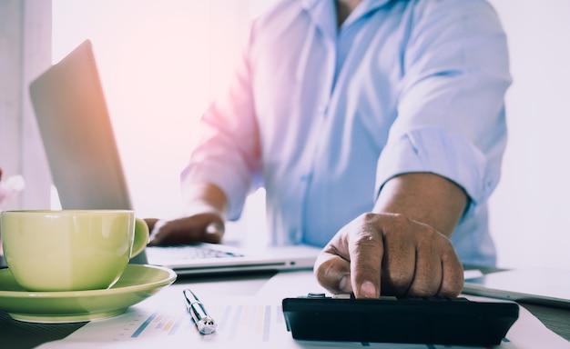 Деловой человек, работающий в офисе с калькулятором и документы на своем столе