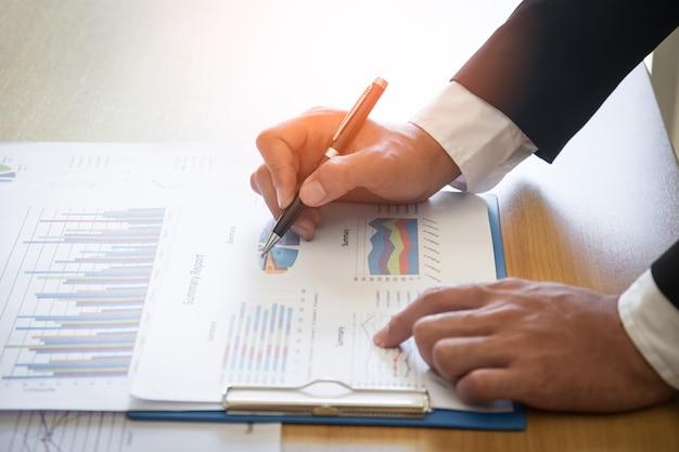 ビジネスマン、グラフとチャートのドキュメントレポート、ビジネスパフォーマンスコンセプトを分析する