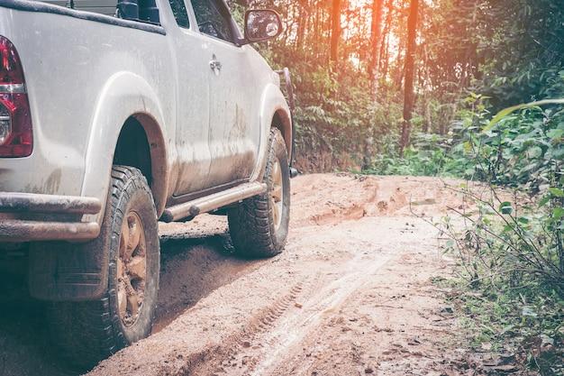 泥と粘土の荒れ果てる森林道でのオフロード車の接写。オフロード旅行のコンセプト。