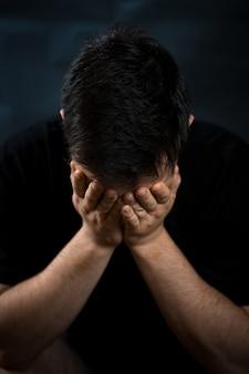 一人で座っている男は悲しみの心配や恐怖を倒し、頭に手を挙げます
