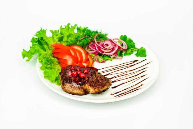 レディと玉ねぎと白い背景の上の新鮮なトマトソースの血色の良いステーキ