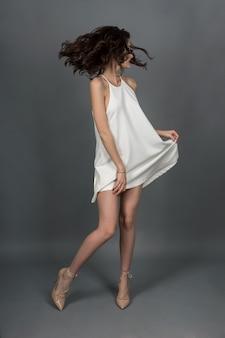 Стройная красивая модель в белом платье и в бежевых туфлях на высоких каблуках позирует на камеру