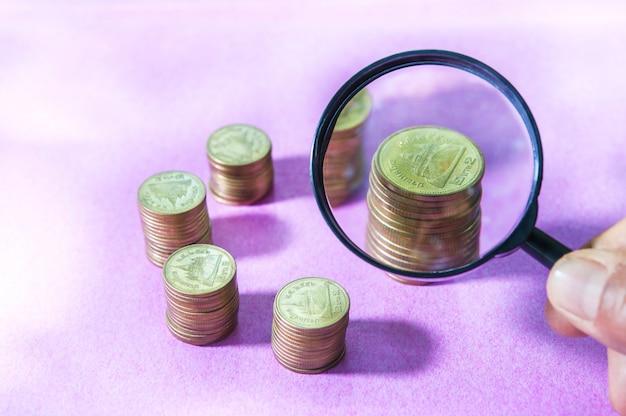 拡大鏡のピンクの背景に成長しているスタッキングコインの投資を検索