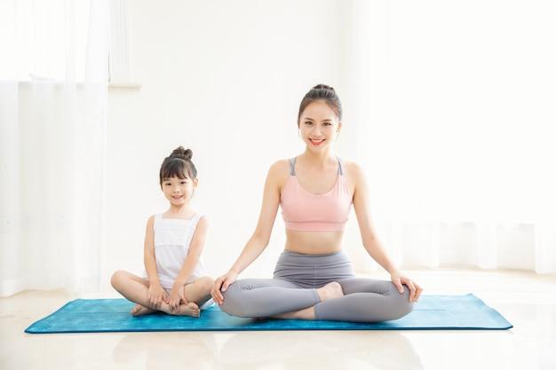 自宅で小さな女の子と母親のスポーツ