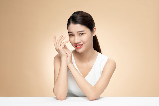 オレンジ色の背景に製品のボトルを保持している美しいアジアの女性