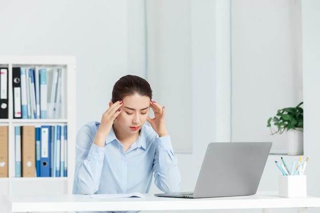 エグゼクティブビジネスの女性がオフィスで頭痛の種を感じる