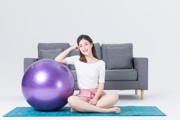 自宅でフィットネスボールとピラト運動をしている美しい若い女性