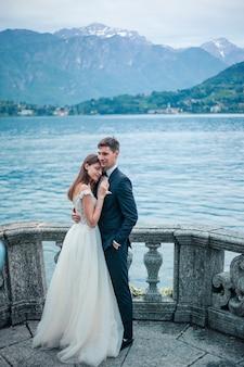 湖と山々の背景を抱いて結婚式のカップル
