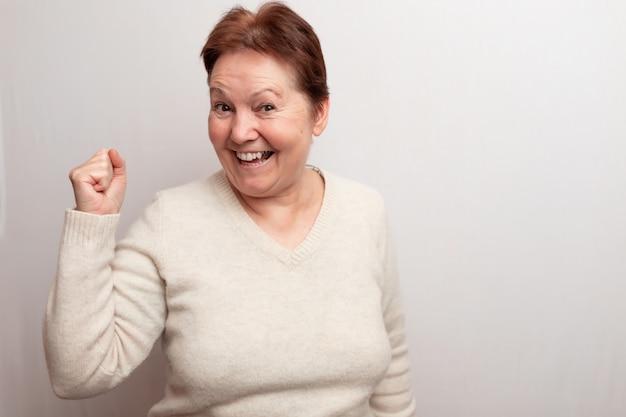 Старая женщина на белом в легком свитере