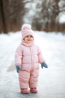 雪に覆われた冬の公園でピンクのジャンプスーツで美しい少女