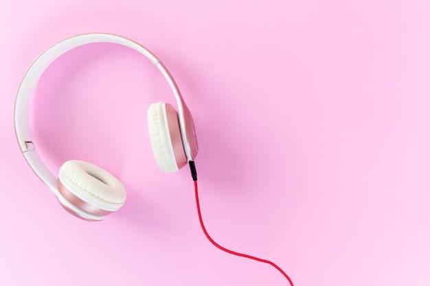 ピンクのヘッドホンと赤いケーブル、パステルカラーのピンクの背景。音楽のコンセプト。