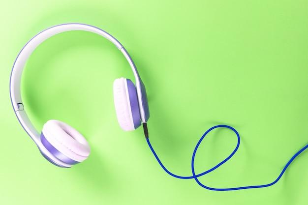 紫色のヘッドフォンと青色のケーブル、パステルカラーの緑色の背景。音楽のコンセプト。
