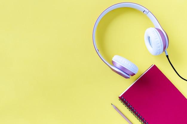 ピンクのヘッドフォン、ノート、鉛筆、パステルカラー、黄色の背景。音楽のコンセプト。