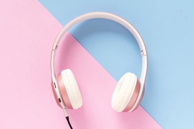ピンクのヘッドフォンとパステルカラーの青とピンクの背景に黒いケーブル。音楽のコンセプト。