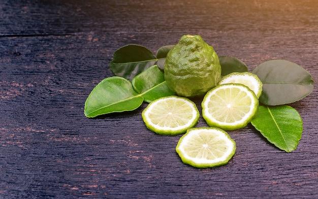 新鮮なベルガモット果実と木製のテーブル背景に緑の葉。空白のコピースペース