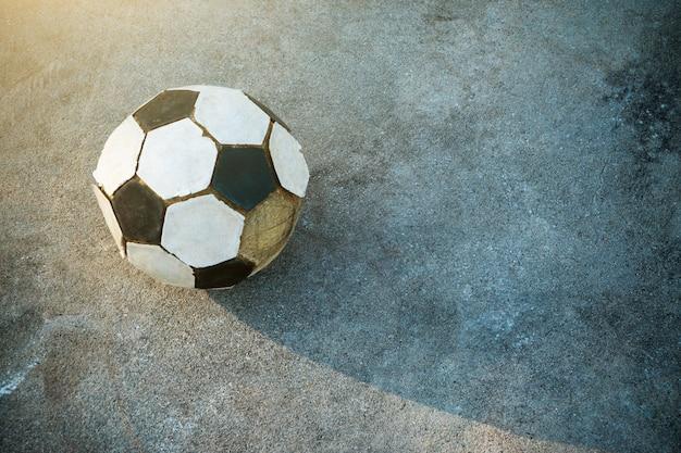 コンクリートの背景と影の古いサッカー
