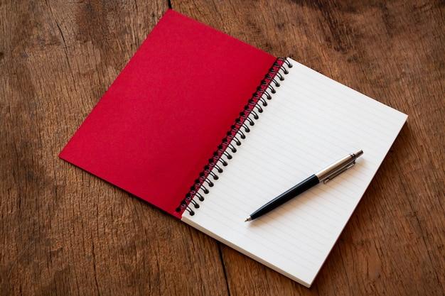 赤いノートと木製のテーブル上のペン
