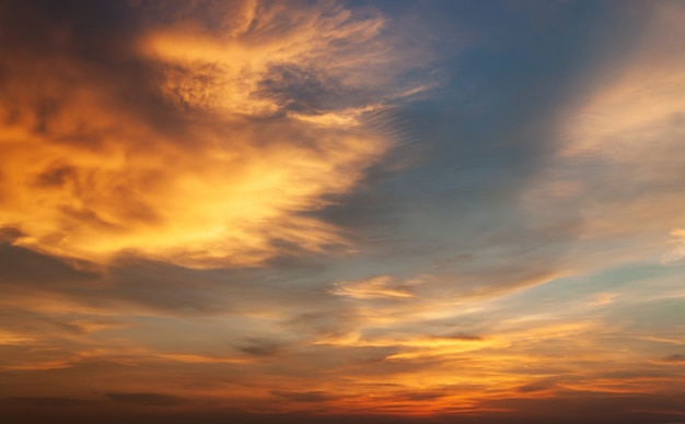 青い空とオレンジ色の夕日を背景に雲。自然と空のコンセプト