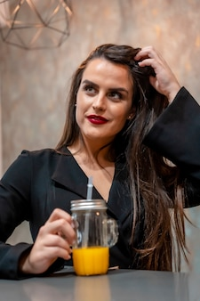 Брюнетка в кафе пьет апельсиновый сок