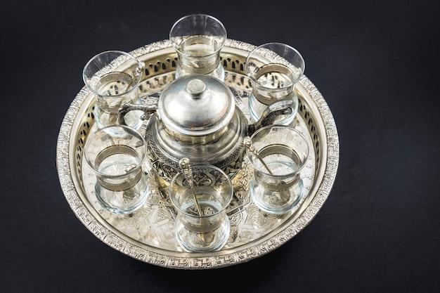 Металлическая кружка и турецкие хрустальные бокалы на круглом подносе
