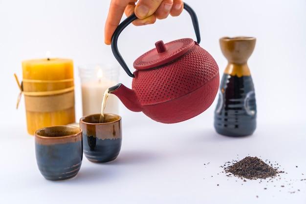 Сервировка японского чая со свечами и чашкой и японскими бокалами