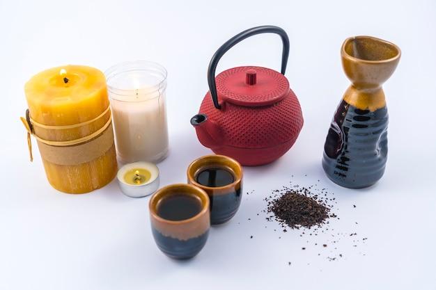 Японский чай со свечами и чашкой и японскими бокалами