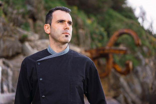 Образ жизни шеф-повара, молодой предприимчивый брюнетка-повар с черным фартуком смотрит вправо