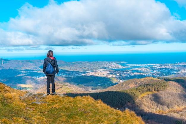 オイアルツンのアイアコハリアの山からフエンテラビアの村を見ている若い登山家。バスク