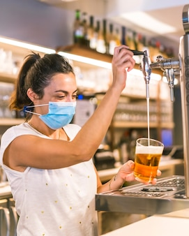 Фотосессия с официанткой с маской в баре. поставить бокал с шестом пива
