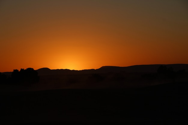 エルグチェビ砂丘のメルズーガ砂漠のベルベル人キャンプからのオレンジ色の空。モロッコ