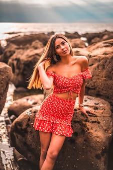 ギプスコアのズマイアの町のイツルルンのビーチで赤いドレスを着た若いブルネットの白人女性。バスク。日没時の海の岩の横にあるライフスタイルセッション