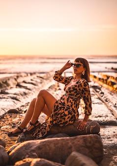 Летний образ жизни на пляже у скал молодой брюнетки кавказской женщины в леопардовом платье