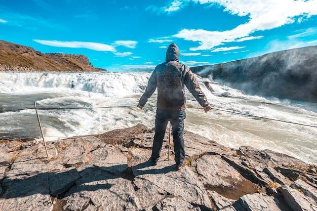 Молодой человек над водопадом гульфосс в золотом круге на юге исландии