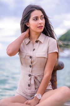 ライフスタイル、海沿いに茶色のオーバーオールを持つブルネットの肖像画