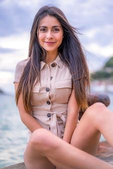ストリートスタイル、夏の海で茶色の短いオーバーオールで座っている若いブルネットの白人女性