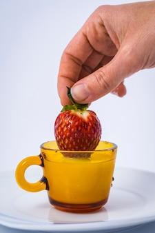 白の女性の手でミルクカップの中のイチゴ