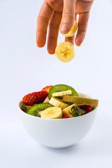 女性の手でフルーツを紹介、キウイ、イチゴ、バナナのフルーツサラダのレシピ