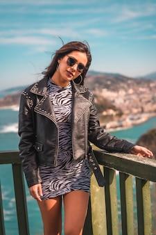 ストリートスタイル、コーカサス地方のブルネット、デニムジャケットとサングラス、サンセバスチャンの街を高台から見る