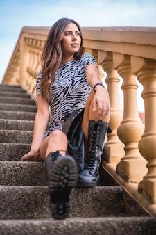 Улыбающаяся брюнетка сидит на лестнице в платье и высоких кожаных сапогах, смотрит вправо