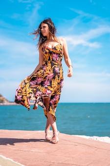 ストリートスタイル、夏の風の強い朝に海岸沿いを散歩する美しいドレスを着たスリムな若いブルネット