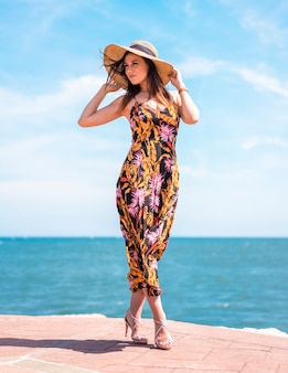 ストリートスタイル、美しい花柄のドレスでスリムな若いブルネットと海を背景に帽子のポーズ