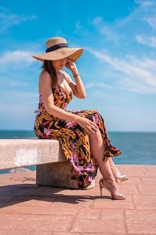 ライフスタイル、花柄のドレスに座っているかなり若いブルネットと海沿いの麦わら帽子