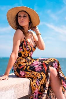 ライフスタイル、ドレスと海沿いの麦わら帽子のかなり若いブルネット