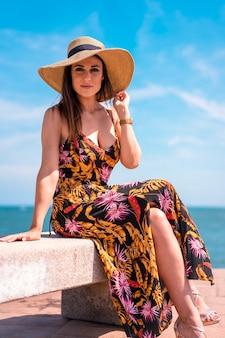 ドレスと海沿いの麦わら帽子の若いブルネットの女性