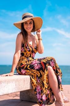 海沿いの麦わら帽子の若いブルネット