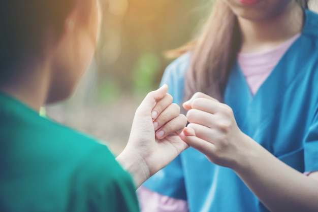 手が自然の背景にお互いの小指を引っ掛ける