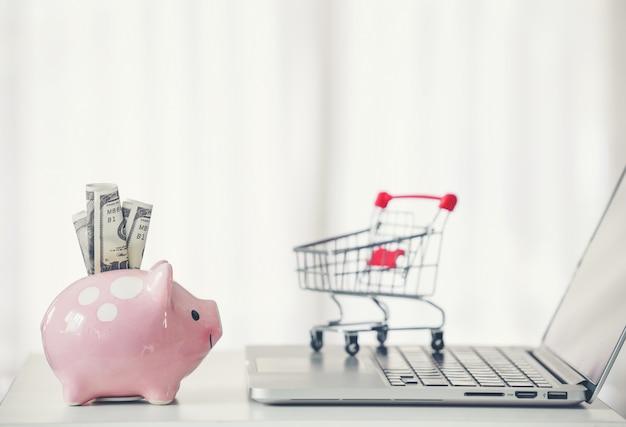 ショッピングカートと貯金箱の机の上のノートパソコン