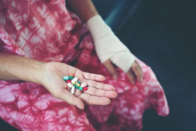上級アジアの女性は手に薬薬を取る